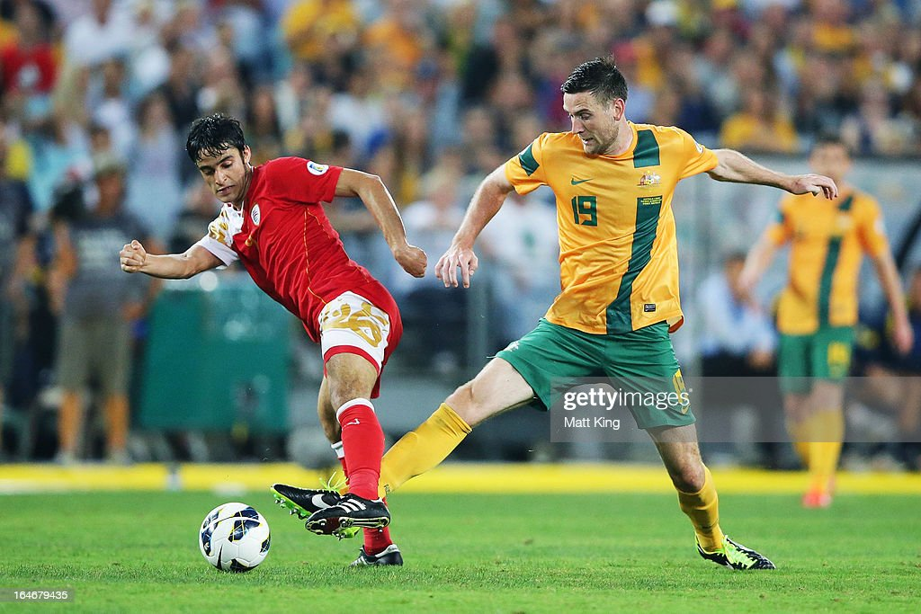 Robbie Cornthwaite of the Socceroos challenges Abdulaziz Al-Miqbali of Oman during the FIFA 2014 World Cup Qualifier match between the Australian Socceroos and Oman at ANZ Stadium on March 26, 2013 in Sydney, Australia.