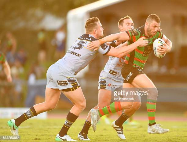 Robbie Farah of the Rabbitohs is tackled by Coen Hess and Scott Bolton of the Cowboys during the round 19 NRL match between the South Sydney...