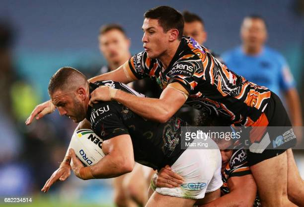 Robbie Farah of the Rabbitohs is tackled by Mitchell Moses of the Tigers during the round ten NRL match between the Wests Tigers and the South Sydney...