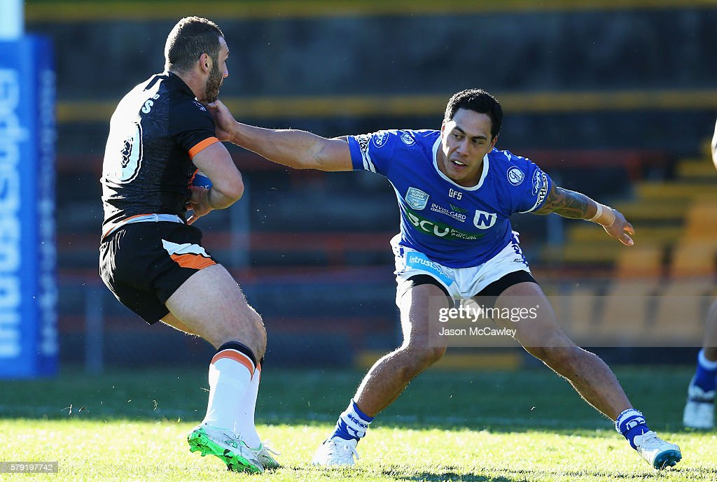 Robbie Farah of the Wests Tigers is tackled by Kurt Kara of the Newtown Jets during the round 19 Intrust Super Premiership NSW match between the Wests Tigers and the Newtown Jets at Leichhardt Oval on July 23, 2016 in Sydney, Australia.