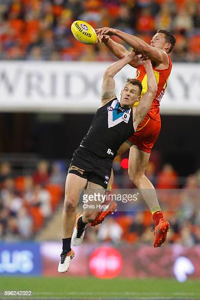 Robbie Gray of the Power and Steven May of the Suns compete for the ball during the round 23 AFL match between the Gold Coast Suns and the Port...