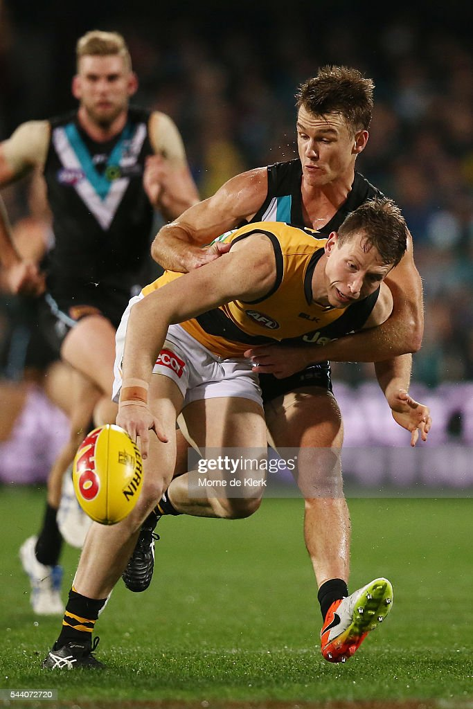 Robbie Gray of the Power tackles Dylan Grimes of the Tigers during the round 15 AFL match between the Port Adelaide Power and the Richmond Tigers at Adelaide Oval on July 1, 2016 in Adelaide, Australia.