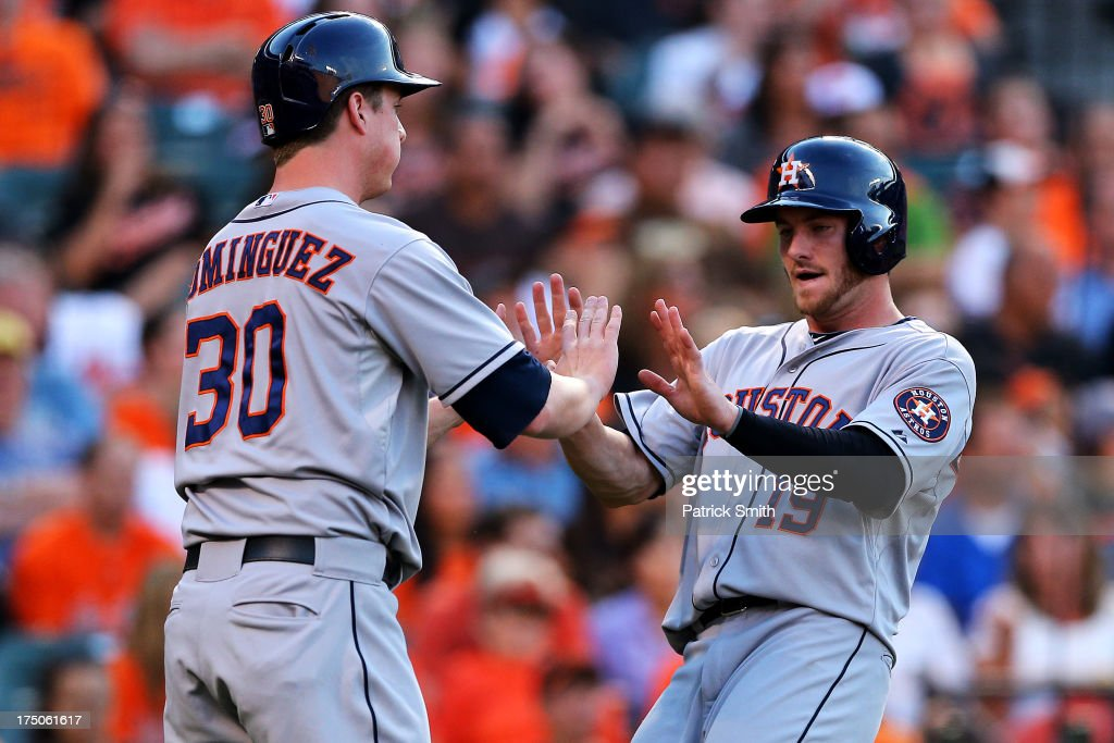 Robbie Grossman #19 of the Houston Astros high-fives teammate <a gi-track='captionPersonalityLinkClicked' href=/galleries/search?phrase=Matt+Dominguez&family=editorial&specificpeople=2934044 ng-click='$event.stopPropagation()'>Matt Dominguez</a> #30 after they both scored off of a hit by teammate Jose Altuve #27 (not pictured) in the third inning against the Baltimore Orioles at Oriole Park at Camden Yards on July 30, 2013 in Baltimore, Maryland.