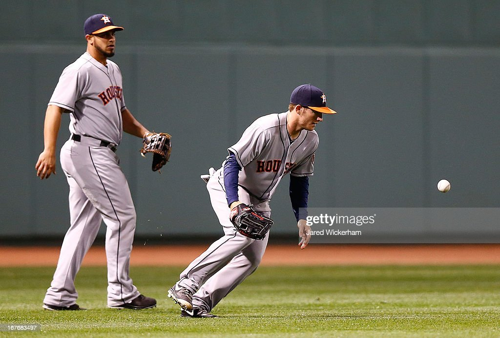 Robbie Grossman #19 of the Houston Astros mishandles a ball hit into left field against the Boston Red Sox during the game on April 27, 2013 at Fenway Park in Boston, Massachusetts.