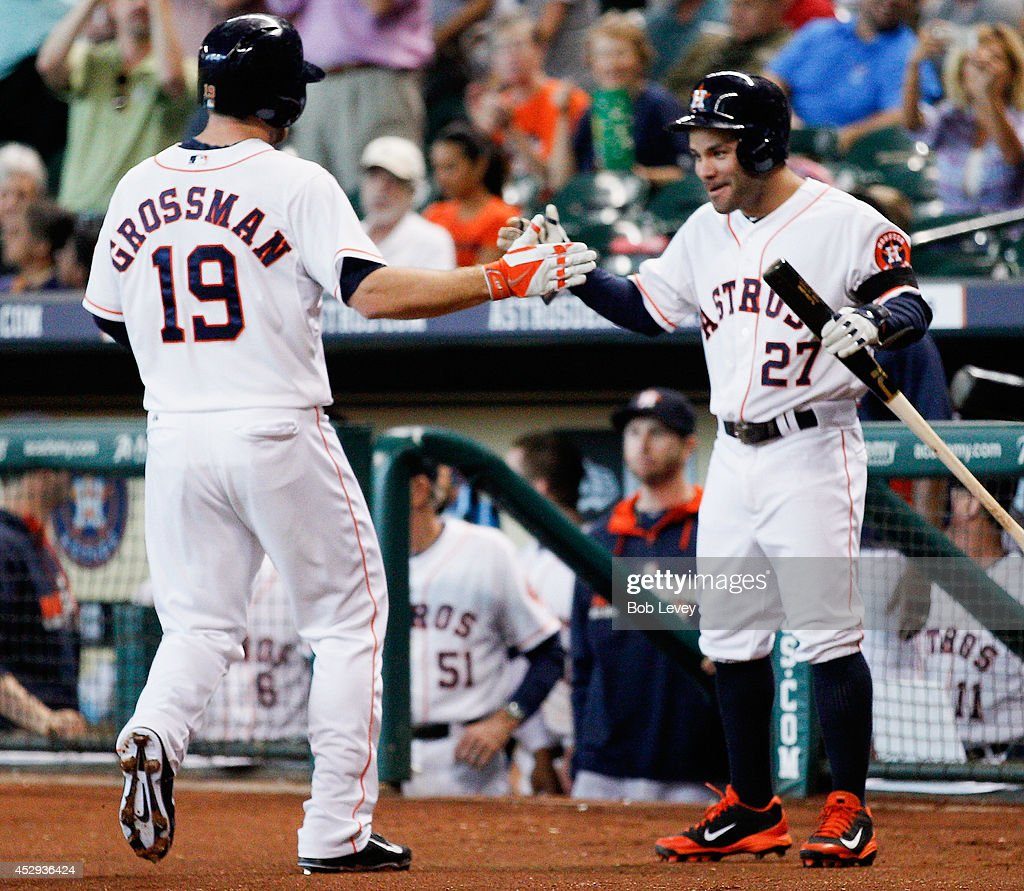 Robbie Grossman #19 of the Houston Astros receives congratulations from Jose Altuve #27 after scoring in the first inning against the Oakland Athletics at Minute Maid Park on July 30, 2014 in Houston, Texas.
