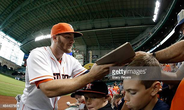 Robbie Grossman of the Houston Astros signs autographs for fans prior to a game against the Texas Rangers at Minute Maid Park on August 30 2014 in...