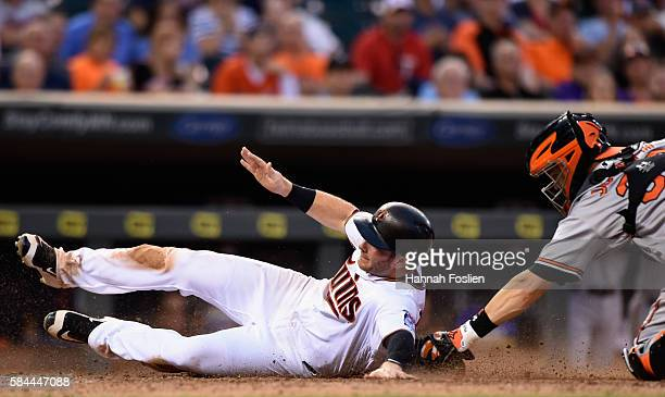 Robbie Grossman of the Minnesota Twins slides safely into home plate to score a run as Caleb Joseph of the Baltimore Orioles applies the tag during...