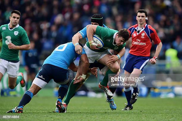 Robbie Henshaw of Ireland is hauled down by Kelly Haimona of Italy during the RBS Six Nations match between Italy and Ireland at the Stadio Olimpico...