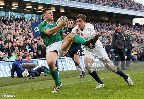 Robbie Henshaw of Ireland takes a high ball to score the opening try despite the efforts of Alex Goode of England during the RBS Six Nations match...