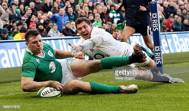 Robbie Henshaw of Ireland touches down the ball to score the opening try despite the efforts of Alex Goode of England during the RBS Six Nations...