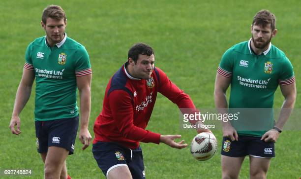 Robbie Henshaw passes the ball watched by Dan Biggar and Elliot Daly during the British Irish Lions training session held at the QBE Stadium on June...