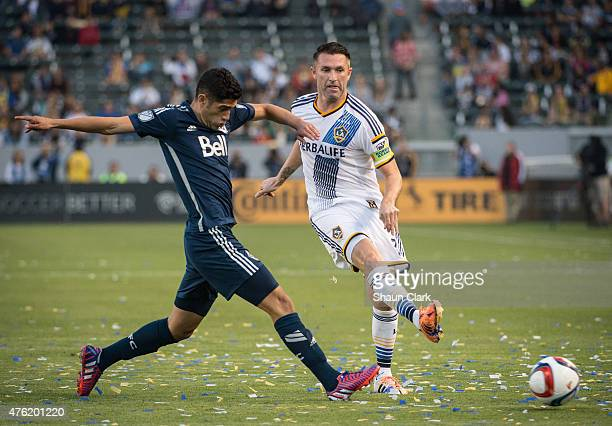 Robbie Keane of LA Galaxy passes the ball as Matias Laba of Vancouver FC closes in during the MLS match at the StubHub Center on June 6 2015 in...