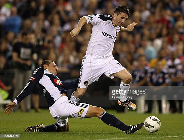 Robbie Keane of the Galaxyis tackled by Peter Franjic of the Victory during the friendly match between the Melbourne Victory and LA Galaxy at Etihad...