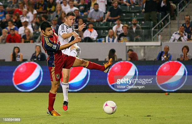 Robbie Keane of the Los Angeles Galaxy shoots and scores against Tony Beltran of Real Salt Lake in the first half during their MLS match against at...