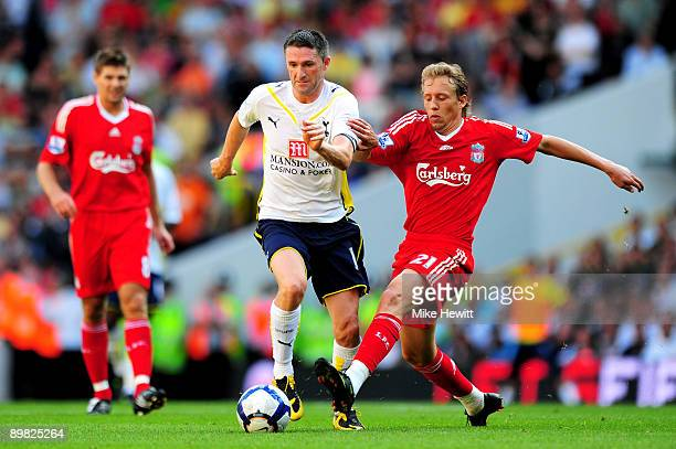 Robbie Keane of Tottenham is challenged by Lucas Leiva of Liverpool during the Barclays Premier League match between Tottenham Hotspur and Liverpool...