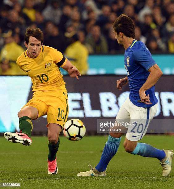 Robbie Kruse of Australia fights for the ball with Rodrigo Caio Russo of Brazil during the friendly international football match between Brazil and...