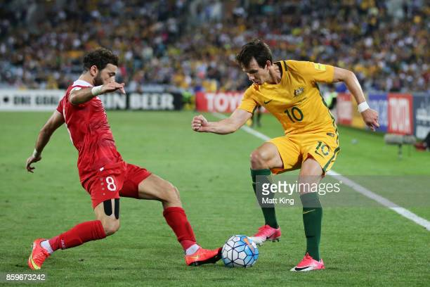 Robbie Kruse of Australia is challenged by Mahmoud Al Mawas of Syria during the 2018 FIFA World Cup Asian Playoff match between the Australian...