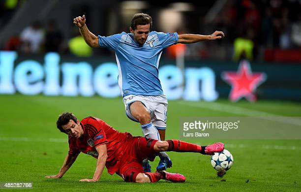 Robbie Kruse of Bayer Leverkusen challenges Senad Lulic of Lazio during the UEFA Champions League qualifying play off round 2nd leg between Bayer...