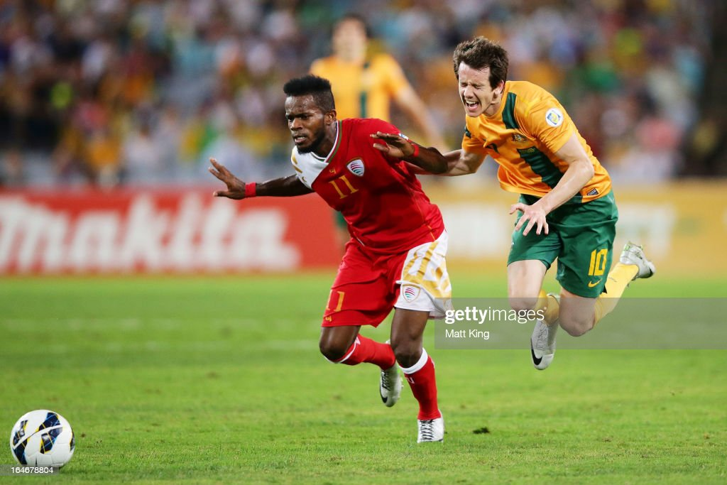Robbie Kruse of the Socceroos is brought down by Saad Al-Mukhaini of Oman during the FIFA 2014 World Cup Qualifier match between the Australian Socceroos and Oman at ANZ Stadium on March 26, 2013 in Sydney, Australia.