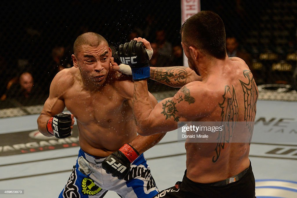 Robbie Peralta punches Estevan Payan in their featherweight bout during the UFC 168 event at the MGM Grand Garden Arena on December 28, 2013 in Las Vegas, Nevada.