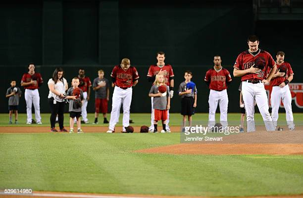 Robbie Ray of the Arizona Diamondbacks and the starting lineup stand for a moment of silence for the victims in the Pulse nightclub terror attack in...