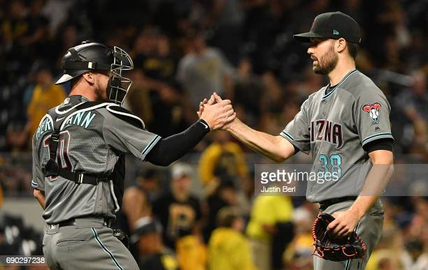 Robbie Ray of the Arizona Diamondbacks celebrates with Chris Herrmann after pitching a complete game shutout against the Pittsburgh Pirates at PNC...