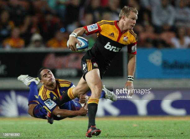 Robbie Robinson of the Chiefs is tackled by Aaron Smith of the Highlanders during the round one Super Rugby match between the Chiefs and the...