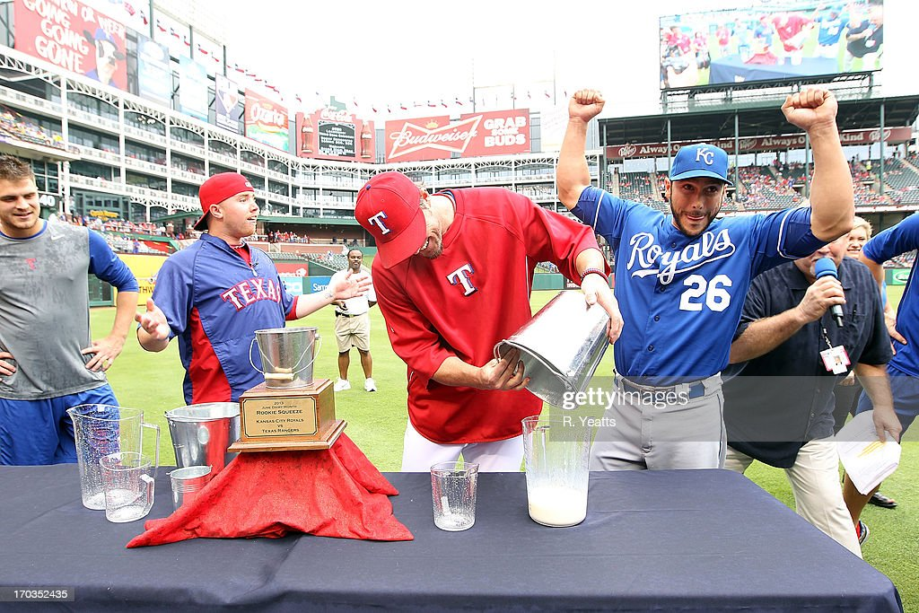 Robbie Ross #46 looks on as <a gi-track='captionPersonalityLinkClicked' href=/galleries/search?phrase=Joe+Nathan&family=editorial&specificpeople=215405 ng-click='$event.stopPropagation()'>Joe Nathan</a> #36 of the Texas Rangers pours <a gi-track='captionPersonalityLinkClicked' href=/galleries/search?phrase=George+Kottaras&family=editorial&specificpeople=730633 ng-click='$event.stopPropagation()'>George Kottaras</a> #26 of the Kansas City Royals milk in for measuring of the Dairy Max cow milking contest event at Rangers Ballpark in Arlington on June 1, 2013 in Arlington, Texas.