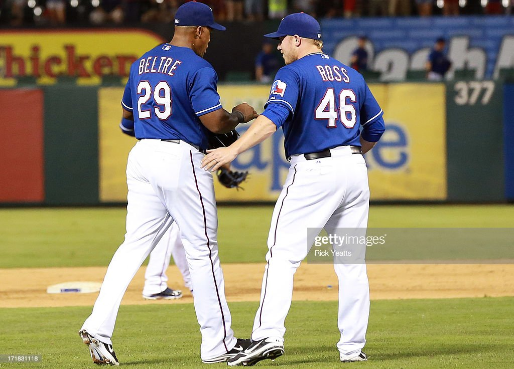 Robbie Ross #46 of the Texas Rangers congratulates teammate <a gi-track='captionPersonalityLinkClicked' href=/galleries/search?phrase=Adrian+Beltre&family=editorial&specificpeople=202631 ng-click='$event.stopPropagation()'>Adrian Beltre</a> #29 for a long throw to first base for the final out in the ninth inning against the Cincinnati Reds at Rangers Ballpark in Arlington on June 28, 2013 in Arlington, Texas.