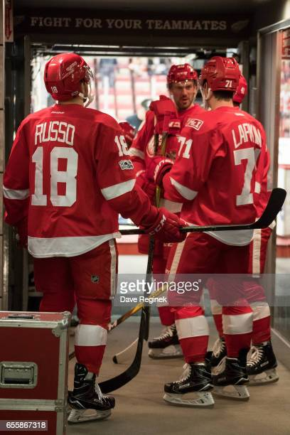 Robbie Russo Dylan Larkin and Drew Miller of the Detroit Red Wings get ready to head out for warm ups before an NHL game against the Colorado...