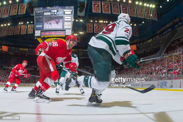 Robbie Russo of the Detroit Red Wings and Jason Pominville of the Minnesota Wild skate after a loose puck during an NHL game at Joe Louis Arena on...