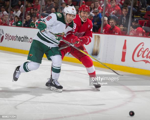 Robbie Russo of the Detroit Red Wings battles for position with Jason Zucker of the Minnesota Wild during an NHL game at Joe Louis Arena on March 26...