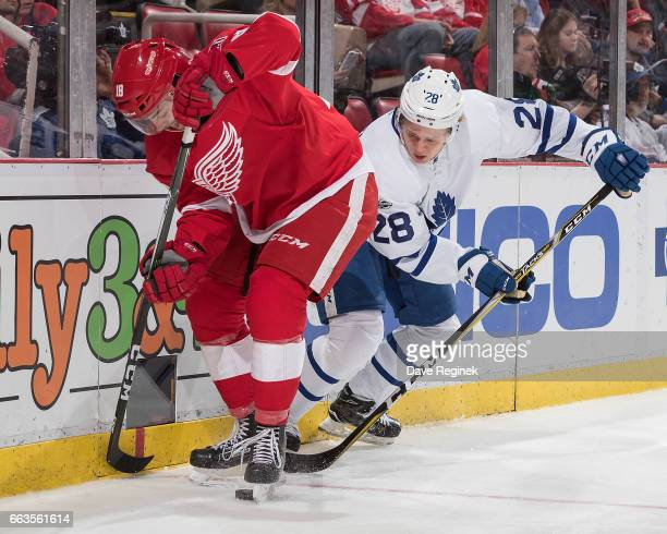 Robbie Russo of the Detroit Red Wings battles for the puck along the boards with Kasperi Kapanen of the Toronto Maple Leafs during an NHL game at Joe...