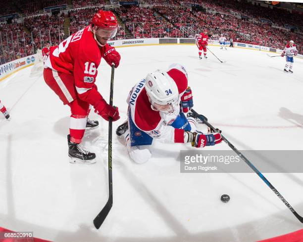 Robbie Russo of the Detroit Red Wings ''battles for the puck with Michael McCarron of the Montreal Canadiens during an NHL game at Joe Louis Arena on...