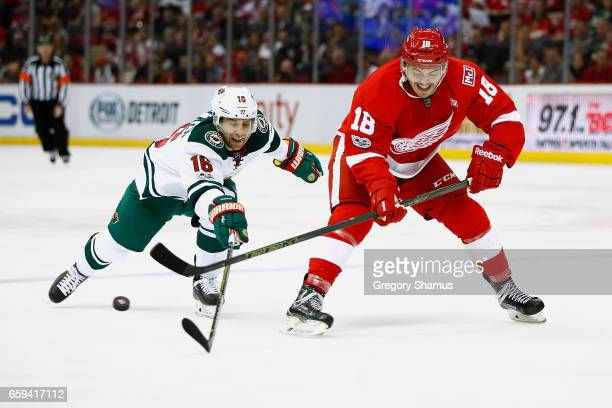 Robbie Russo of the Detroit Red Wings controls the puck in front of Jason Zucker of the Minnesota Wild at Joe Louis Arena on March 26 2017 in Detroit...