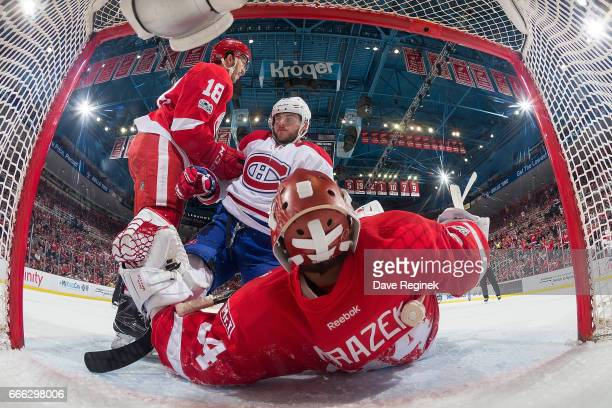 Robbie Russo of the Detroit Red Wings helps up Alex Galchenyuk of the Montreal Canadiens after he crashed into goaltender Petr Mrazek of the Wings...