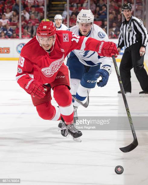 Robbie Russo of the Detroit Red Wings skates after the puck followed by Joel Vermin of the Tampa Bay Lightning during an NHL game at Joe Louis Arena...