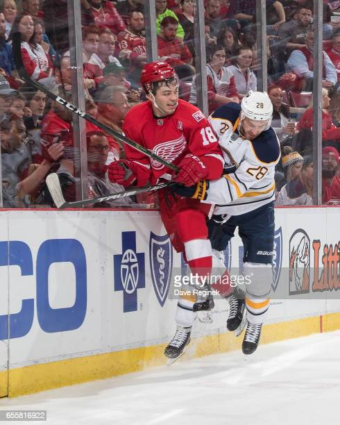 Robbie Russo of the Detroit Red Wings takes a hit against the boards by Zemgus Girgensons of the Buffalo Sabres during an NHL game at Joe Louis Arena...