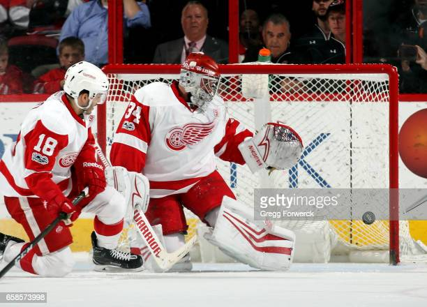Robbie Russo of the Detroit Red Wings watches as Petr Mrazek deflects a Carolina Hurricanes shot during an NHL game on March 27 2017 at PNC Arena in...