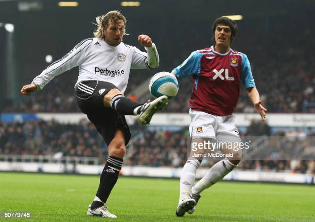Robbie Savage of Derby County hooks in a cross watched by James Tomkins of West Ham United during the Barclays Premier League match between West Ham...