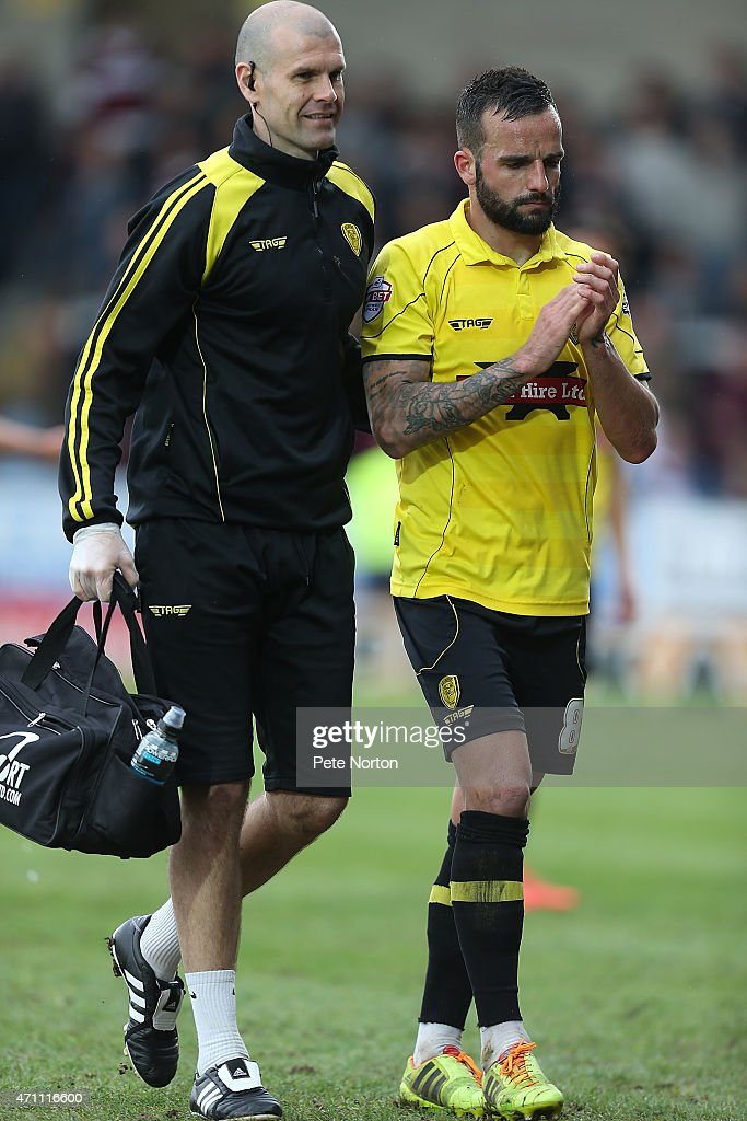 Robbie Weir of Burton Albion leaves the pitch with physio Nick Fenton during the Sky Bet League Two match between Burton Albion and Northampton Town at Pirelli Stadium on April 25, 2015 in Burton-upon-Trent, England.