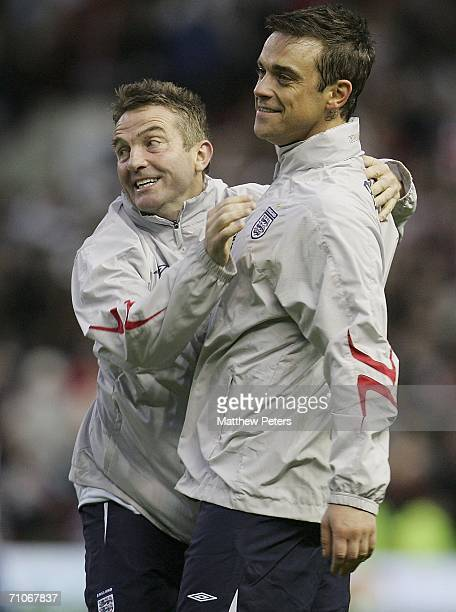 Robbie Williams and Bradley Walsh of England celebrate at the end of the Soccer Aid Unicef and ITV Football Match between England and the Rest of the...