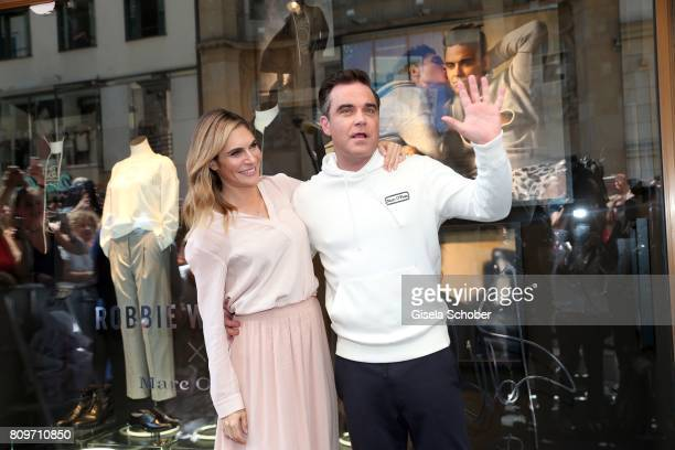 Robbie Williams and his wife Ayda Williams kiss during the launch of the Marc O'Polo 50th anniversary special edition sweatshirt on July 6 2017 in...