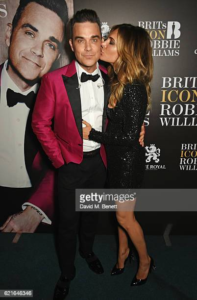 Robbie Williams and wife Ayda Field pose backstage at a special gig presented by Cafe Royal where Robbie will be awarded the BRITs Icon Award at the...