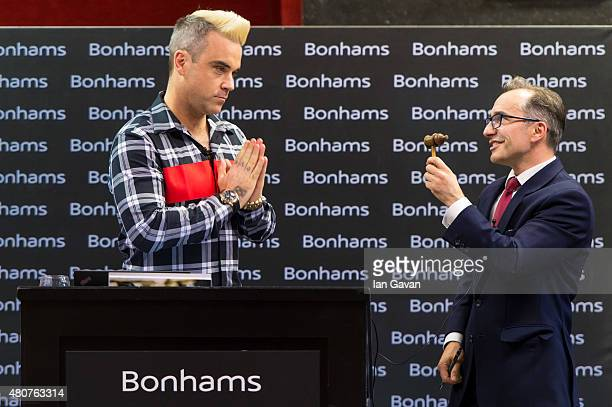Robbie Williams joins auctioneer James Stratton during the auction of Robbie Williams memorabilia in aid of the Donna Louise Children's Hospice at...