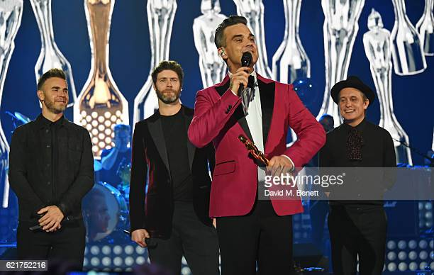 Robbie Williams receives the BRITs Icon Award from fellow Take That members Gary Barlow Howard Donald and Mark Owen at a special gig presented by...