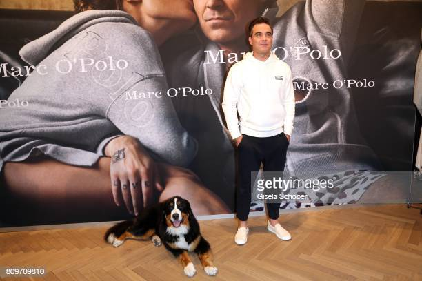 Robbie Williams with his dog 'Showbiz' during the launch of the Marc O'Polo 50th anniversary special edition sweatshirt on July 6 2017 in Munich...