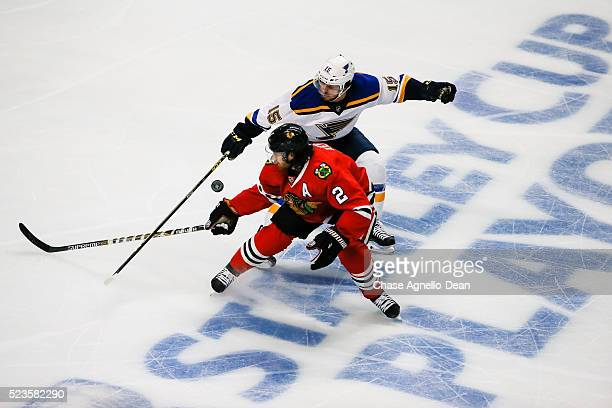 Robby Fabbri of the St Louis Blues and Duncan Keith of the Chicago Blackhawks swing at the puck in the first period of Game Six of the Western...
