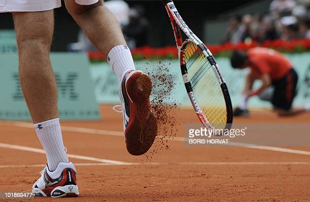 US Robby Ginepri knocks clay out of the treads of his shoe during his men's fourth round match against Serbia's Novak Djokovic in the French Open...