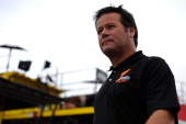 Robby Gordon driver of the Speed Energy Dodge walks through the garage area during practice for the NASCAR Sprint Cup Series Sylvania 300 at New...